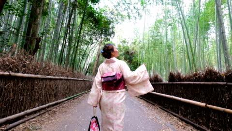 vidéos et rushes de 4 k suivi de tir: une femme asiatique kimono robe parcouru arashiyama de bosquets de bambous et de sagano. culture japonaise - japon