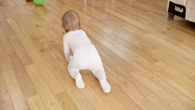 SLO MO Following a baby crawling across the floor video