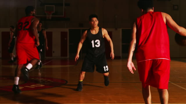Following a basketball player dribble down the court during a game, slow motion video
