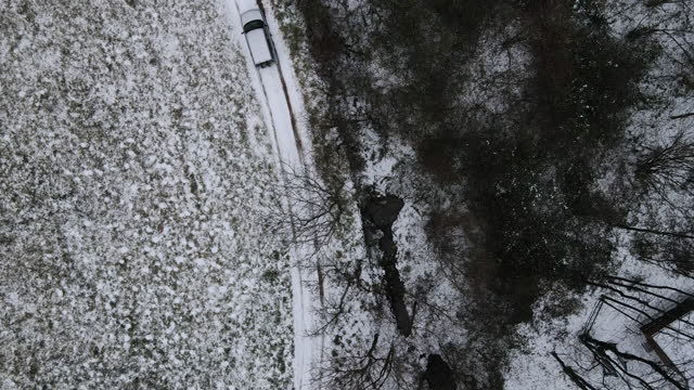 Following a Car Driving on Road Covered With Snow From High Angle View video