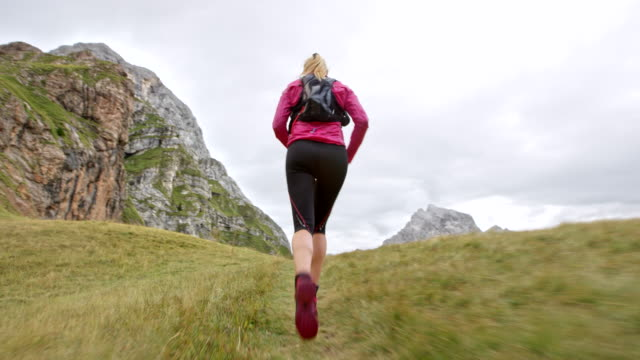 Following a female runner running on a grassy trail of a high mountain ridge Wide low angle handheld shot following a female runner running on a grassy terrain of a high mountain ridge. Shot in Slovenia. pedal pushers stock videos & royalty-free footage