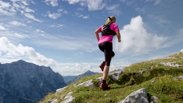 slo mo following a female runner running up a high mountain ridge in sunshine - in cima video stock e b–roll
