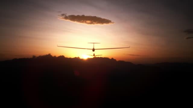 vidéos et rushes de suivant un plan de planeur en coucher de soleil - glisser