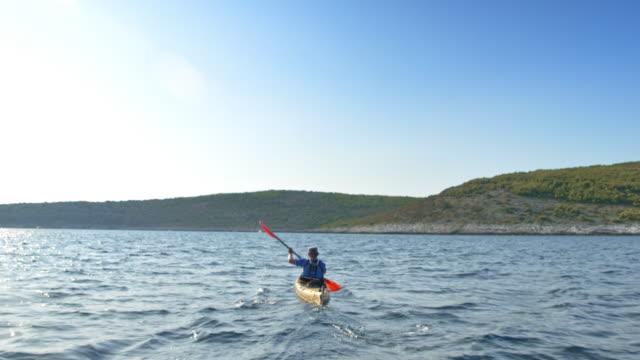 Following a kayaker paddling his sea kayak in sunshine