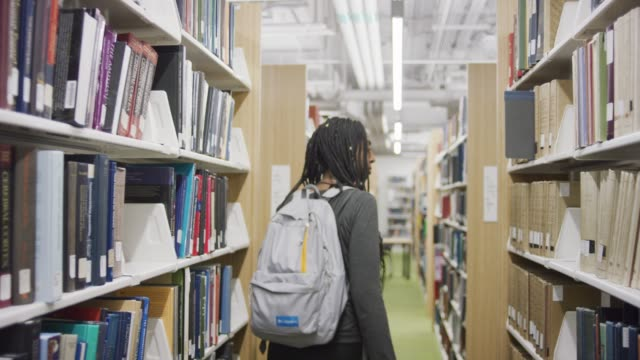 Following a Woman Looking for Books in a Library
