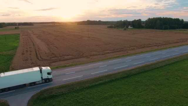 Following and Aerial Shot  of a Truck Driving on Highway. Beautiful Field Landscape and Setting Sun is Seen. video
