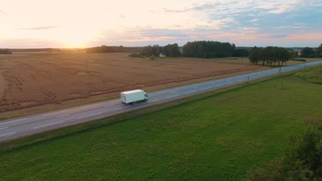 vídeos de stock, filmes e b-roll de tiro aéreo e seguir de um caminhão, dirigindo na estrada. bela paisagem de campo e pôr do sol é visto. - caminhonete pickup
