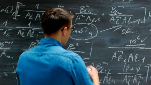 次のチョークと書き込み複雑な数式を持っている手のクローズ アップ ショット/黒板上の方程式。 - 数学の授業点の映像素材/bロール