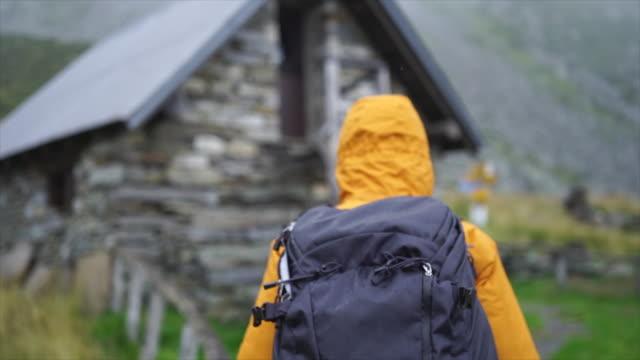 vídeos de stock e filmes b-roll de following female hiker walking towards stone hut in rainy weather - mochila saco