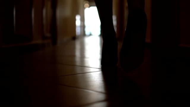 efter fot spår av oigenkännlig kvinna i höga kullar skor som går längs gång vägen i den mörka korridoren, slow motion - människofot bildbanksvideor och videomaterial från bakom kulisserna