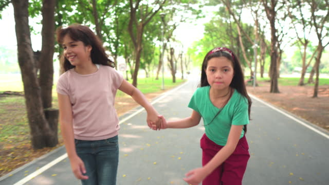following front view: happy teenager girl and friend playing roller skate in public park in morning of weekend - preadolescente video stock e b–roll