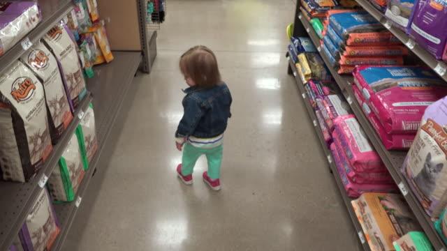 vídeos de stock e filmes b-roll de following jean jacket toddler at pet store thru dry dog food aisle. - criança perdida