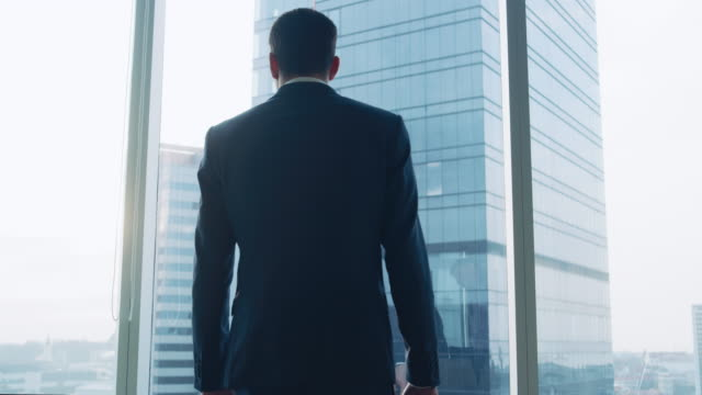 Following Low Angle Elevating Shot of the Confident Businessman in a Suit Walking Through His Office, Putting Hands in Pockets and Looking out of the Window Thoughtfully, Contemplating New Business Deals and Future Contracts.