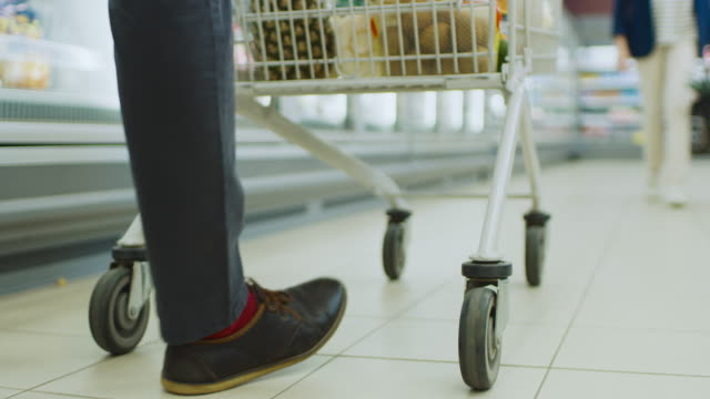 following low ground shot at the supermarket: of the legs and shopping cart full of products moving through frozen goods section of the store. - замороженные продукты стоковые видео и кадры b-roll