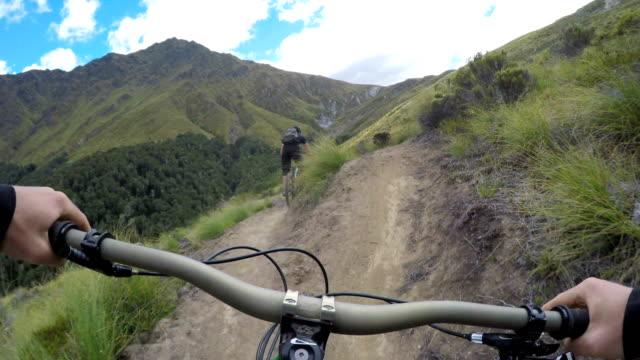 pov following mountain biker down mountain trail - adrenalina video stock e b–roll