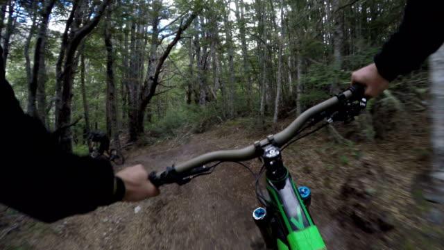 pov following mountain biker down technical trails - andare in mountain bike video stock e b–roll