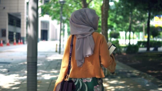efter bakre skott av unga asiatiska flicka promenader med bok utomhus - hijab bildbanksvideor och videomaterial från bakom kulisserna