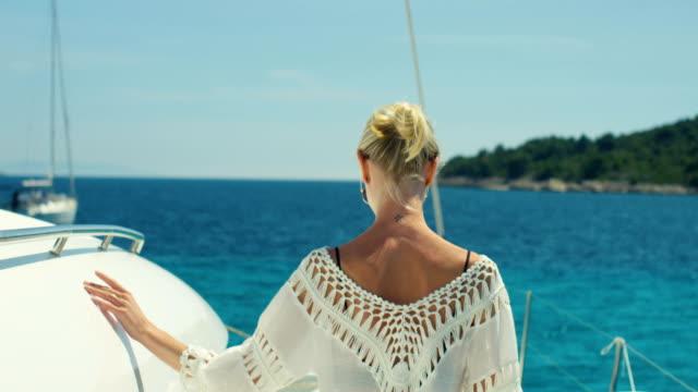 Après le tir d'une belle femme marchant sur le pont du Yacht. Soleil, îles et la mer d'Azur en arrière-plan. - Vidéo