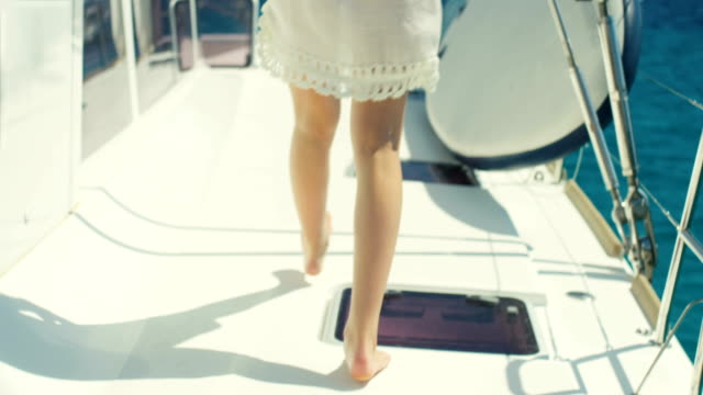 Following Shot of a Beautiful Woman Walking on the Yacht's Deck. Sun Shines, Islands and Azure Sea in the Background.