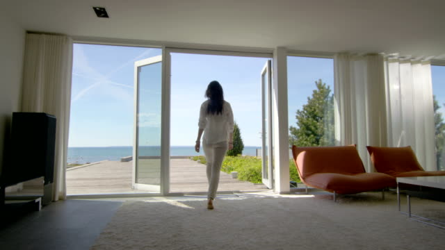 Following Shot of a Beautiful Young Woman Running out of Her House onto the Terrace with a Seaside View.