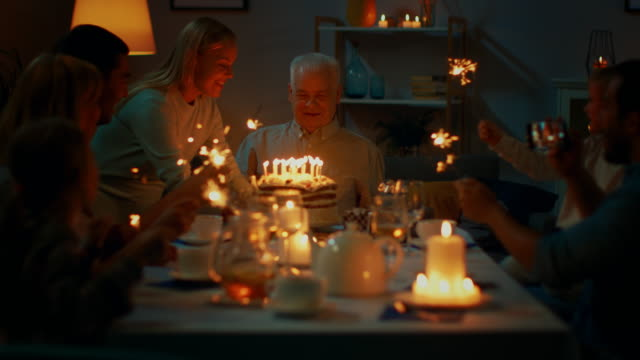 Following Shot of a Daughter Bringing Birtday Cake with Candlelights to Her Senior Father. Family Dinner and Celebration, People Gathered at the Evening Dinner Table. Following Shot of a Daughter Bringing Birtday Cake with Candlelights to Her Senior Father. Family Dinner and Celebration, People Gathered at the Evening Dinner Table. Shot on RED EPIC-W 8K Helium Cinema Camera. happy birthday stock videos & royalty-free footage