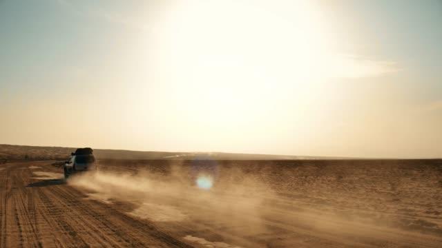 following shot of a moving offroad 4wd silver car on desert and dust trail - wiejska droga filmów i materiałów b-roll