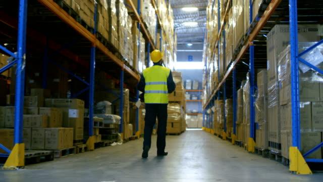 vídeos y material grabado en eventos de stock de siguiente disparo de un trabajador de almacén que lleva casco duro caminando por filas de bastidores de almacenamiento. - gerente de cuentas