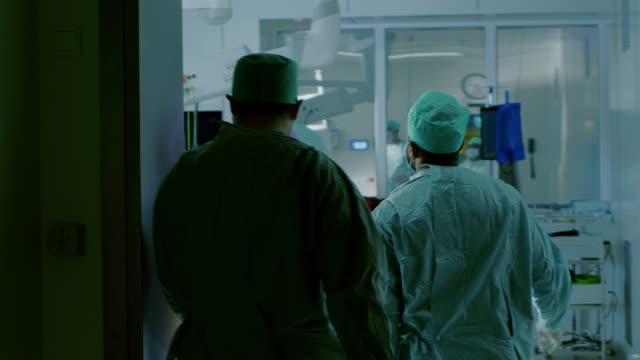 following shot of diverse team of surgeons and assistants walk into operating room where patient waits, they put him under anesthesia and start surgery. real modern hospital with authentic equipment. - zabieg medyczny filmów i materiałów b-roll