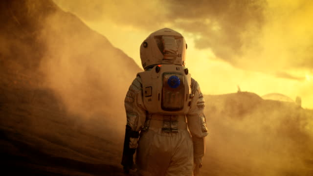 Following Shot of Female Astronaut in Space Suit Confidently Walking on Mars, Turing Around and Looking into the Camera. Red Planet Covered in Gas and Smoke.