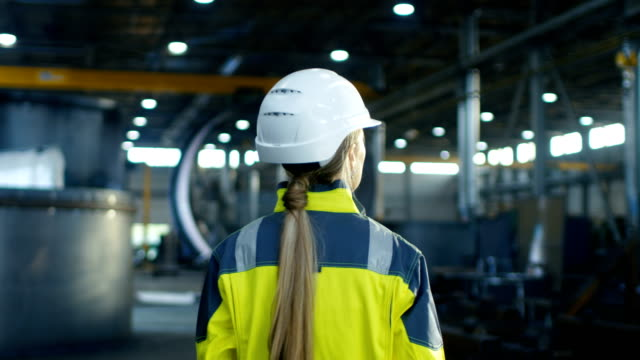 Following Shot of Female Industrial Worker in the Hard Hat Walking Through Heavy Industry Manufacturing Factory. In the Background Various Metalwork Project Parts Lying