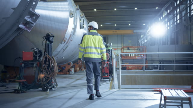 following shot of heavy industry engineer walking through pipe manufacturing factory. modern facility for design and construction of large diameter oil, gas and fuels transport pipeline. slow motion - attrezzatura industriale video stock e b–roll