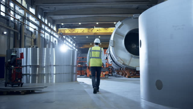 Following Shot of Heavy Industry Engineers Walking Through Manufacturing Factory. In the Background Professionals Working on Construction of Oil, Gas and Fuel Pipeline Transportation Products video