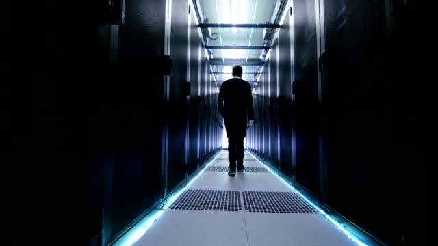それの次のショットは、ラック マウント型サーバの行を持つデータ センターの廊下を歩くエンジニア リングします。 - スーパーコンピューター点の映像素材/bロール