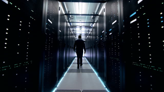 Following Shot of IT Engineer Walking Through Data Center Corridor with Rows of Rack Servers. Opens Laptop.
