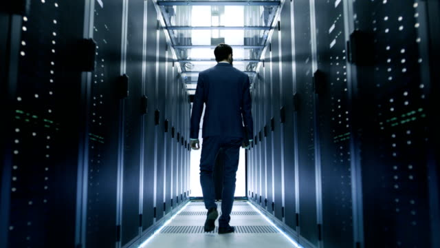 Following Shot of IT Engineer Walking Through Data Center with Rows of  Working Rack Servers on Both Sides. video
