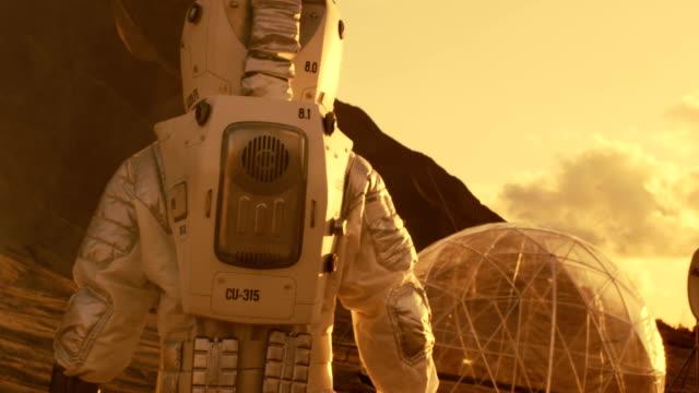 anschluss an schuss des astronauten auf dem mars zu fuß in richtung seiner basis / forschungsstation, schaut sich um. erste bemannter mission zum mars, technologischen fortschritt bringt, kolonisierung des weltraums. - erforschung des weltalls stock-videos und b-roll-filmmaterial