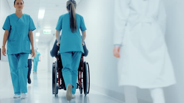 vídeos de stock e filmes b-roll de following shot of the female nurse moving patient in the wheelchair through the hospital corridor. doing procedures. bright modern hospital with friendly staff. - medicare