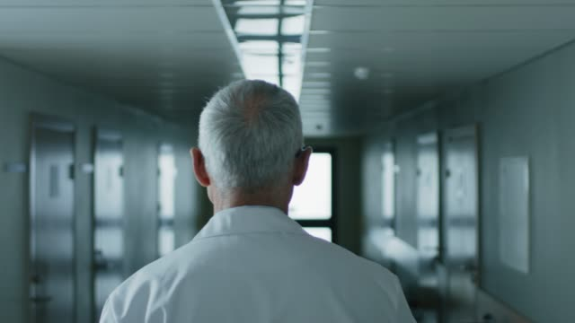 Following Shot of the Professional Male Doctor Walking Through Hospital Hallway. Portrait Footage.