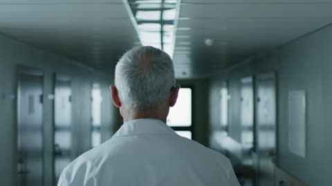 vídeos de stock e filmes b-roll de following shot of the professional male doctor walking through hospital hallway. portrait footage. - andar