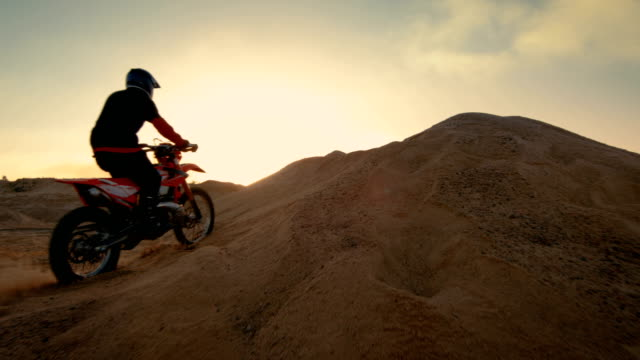 following shot of the professional motocross motorcycle rider driving over the dune and further down the off-road track. it's sunset and track is covered with smoke/ mist. - freestyle motocross video stock e b–roll