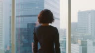 istock Following Shot of the Successful Businesswoman in a Stylish Dress Walking Through Her Office and Looking out of the Window Thoughtfully. Modern Business Office with Personal Computer and Big City View. 1006574900