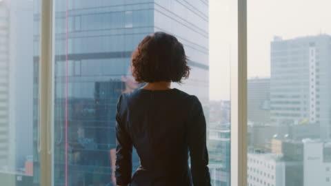 stockvideo's en b-roll-footage met shot van de succesvolle zakenvrouw in een stijlvolle jurk lopen via haar kantoor en kijken uit het venster zorgvuldig volgen. moderne kantoor met personal computer en uitzicht op de grote stad. - modern