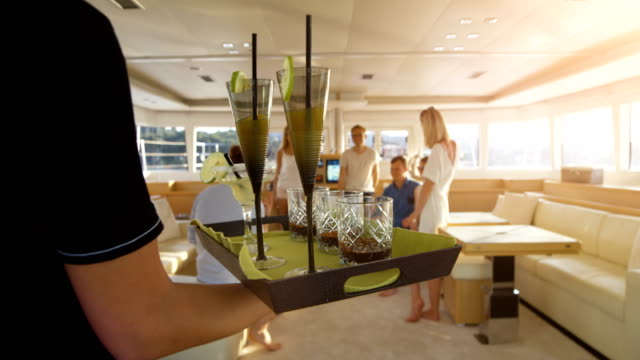 following shot of the waiter walking with a tray full of exotic cocktails, serving them to a company of young people on a yacht. - cruise video stock e b–roll