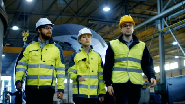 following shot of three engineers walking through heavy industry manufacturing factory. in the background welding work in progress, various metalwork, pipeline/ barrel components. slow motion. - деятельность стоковые видео и кадры b-roll