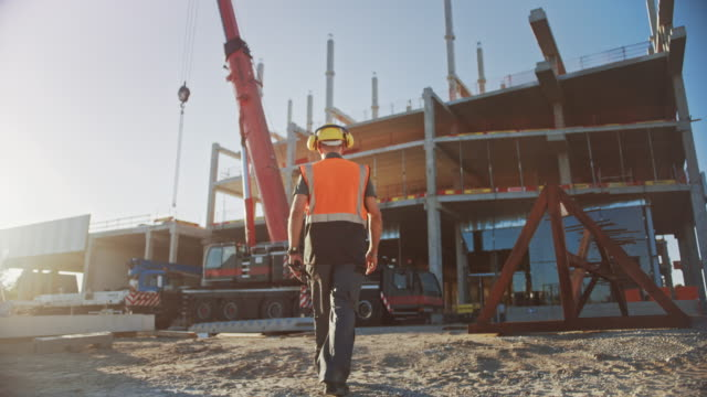 Following Shot: Worker Contractor Wearing Hard Hat and Safety Vests Walks on Industrial Building Construction Site. In the Background Crane, Skyscraper Concrete Formwork Frames