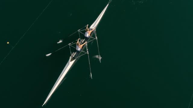 vídeos de stock, filmes e b-roll de antena seguindo dois atletas de remo em um lago em um double scull - remo atividade física