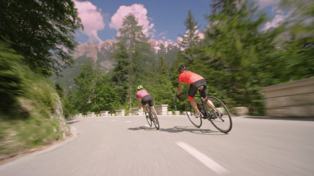 following two female road cyclists descending the mountain on a picturesque mountain road - ciclismo su strada video stock e b–roll