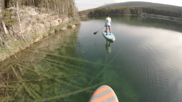 POV following woman stand up paddle boarding across alpine lake They perform yoga moves while balancing pedal pushers stock videos & royalty-free footage