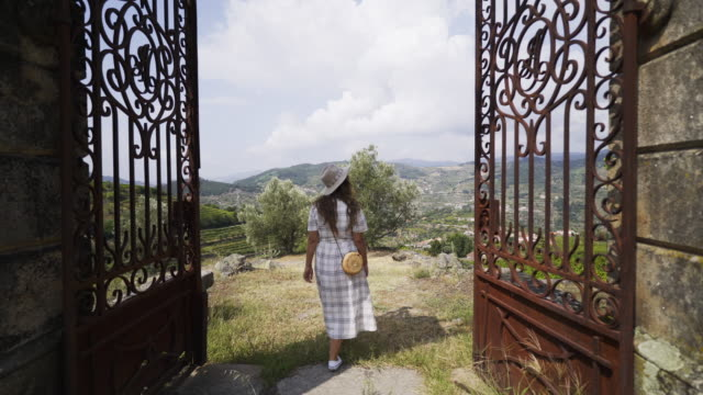 Following young woman entrancing on ancient villa Following from the back young lady walking through gates on vineyards. Entrancing traditional Portugal Quinta- Villa in valley of Douro river in winemaking region human back stock videos & royalty-free footage