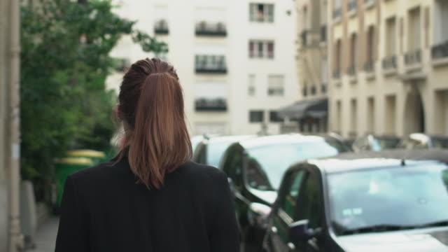 stockvideo's en b-roll-footage met follow-up shot van classy zelfverzekerde blanke vrouw met zonnebril, sproeten, piercings, paardenstaart, jas en rood haar wandelen door de straat, tijdens zonnige dag in parijs. slow motion achteraanzicht. - paardenstaart haar naar achteren